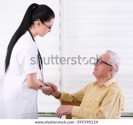 Young pretty nurse holding hands of senior man. Senior care concept - stock photo