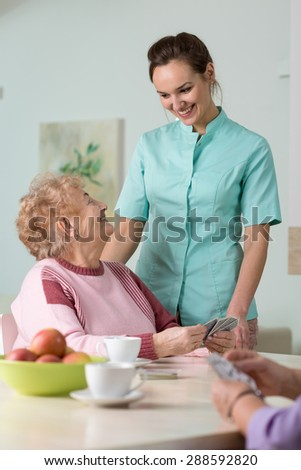 Young pretty nurse taking care of her aged female patient - stock photo