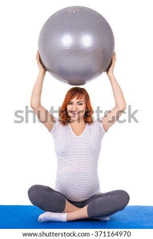 young pretty pregnant woman doing exercises with fitball isolated on white background