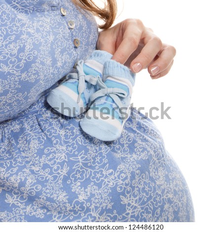 young pretty pregnant woman with the baby bootees in her hand - stock photo