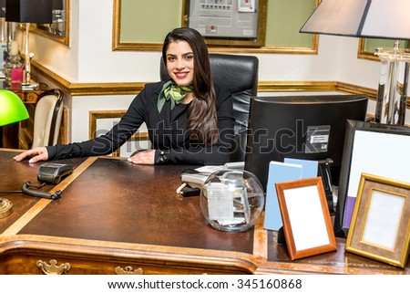 Young pretty receptionist at her work desk - stock photo