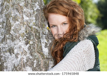 Young pretty  red haired woman embraces a birch tree - stock photo