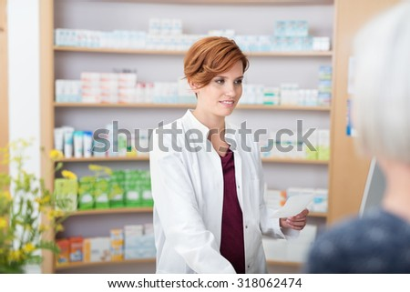 Young pretty redhead female pharmacist assisting on older woman with her prescription medication as she smiles at her over the counter