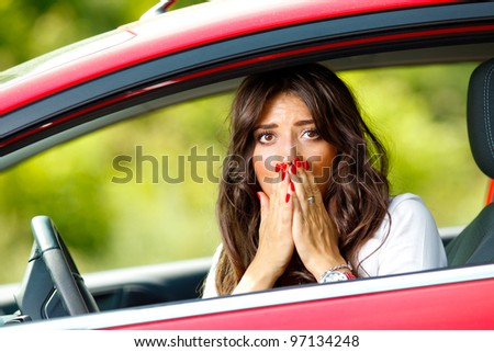 Young pretty scared woman sitting in the red car - stock photo