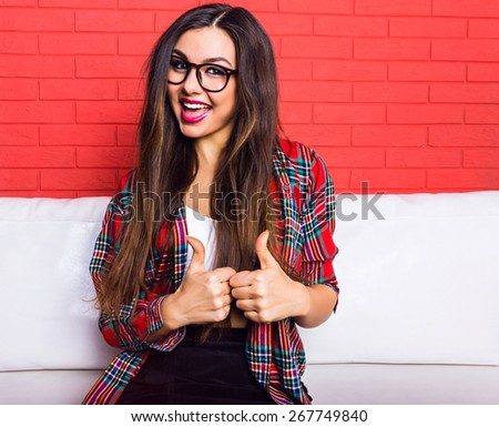 Young pretty seductive hipster woman having fun and showing okay science, wearing plaid shirt and clear glasses, long hairs and bright make up. Red urban wall background. - stock photo