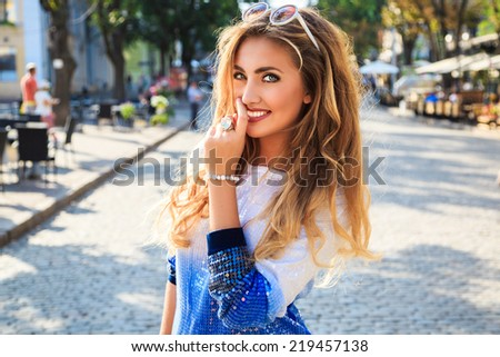 Young pretty seductive woman with amazing fluffy blonde curled hairstyle, perfect skin and natural make up, explore european city alone, at nice sunny day, wearing bright sweater and sunglasses. - stock photo