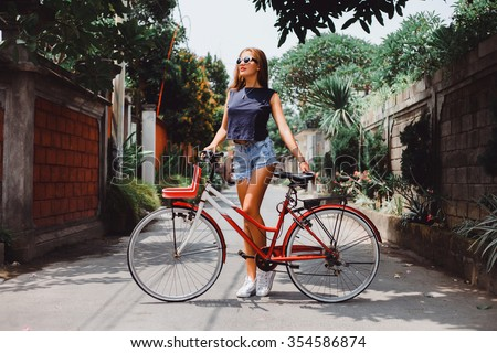 Young pretty sensual blond girl posing outdoor  with red vintage bicycle in a blue shirt in white sneakers, fashionable stylish clothes sunglasses red lipstick on her lips  - stock photo