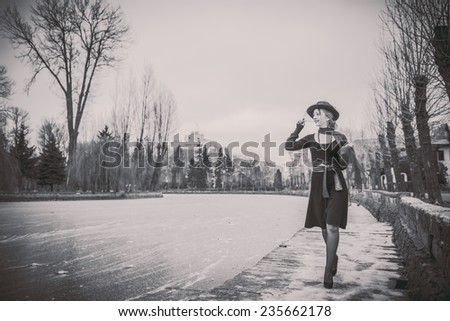 Young pretty sexy lady in black dress outdoor with frozen lake onbackground, black and white