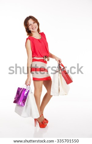 young pretty smilimg woman in red dress and shoes standing with shopping bags on light background