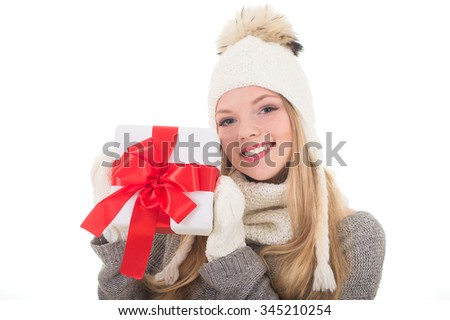 Young pretty smiling beautiful woman in white knitted hat holds new year christmas gift with red ribbon