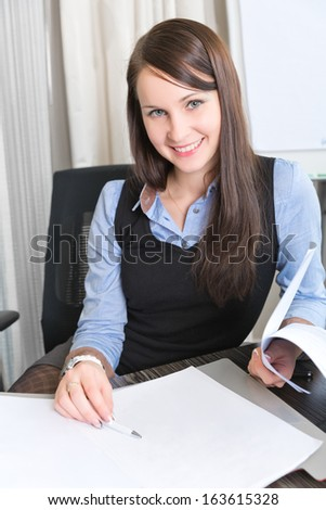 Young pretty smiling business woman with notebook in the office - stock photo