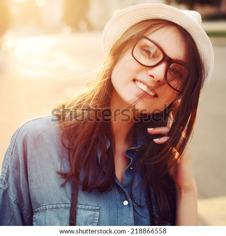 Young pretty smiling fashion sensual hipster girl closeup portrait in city warm sunny weather dressed in hat and glasses