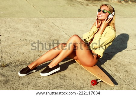 Young pretty smiling fashion tanned sport style woman dressed in bikini sitting on longboard having fun smiling and listening music in hot summer - stock photo