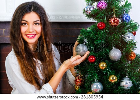 Young pretty smiling girl with bright make up and amazing brunette long hairs decorates the Christmas tree. - stock photo