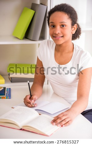 Young pretty smiling schoolgirl sitting at the table and writing homework on colorful background.