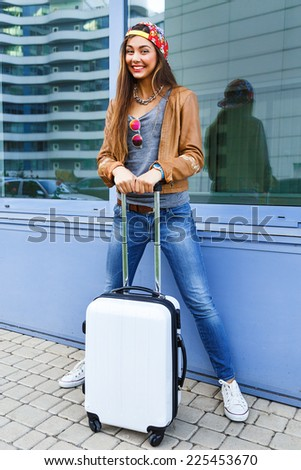 Young pretty smiling teen pretty brunette girl posing with her luggage near air port, wearing bright swag styled casual clothes, ready for travel and new emotions. - stock photo