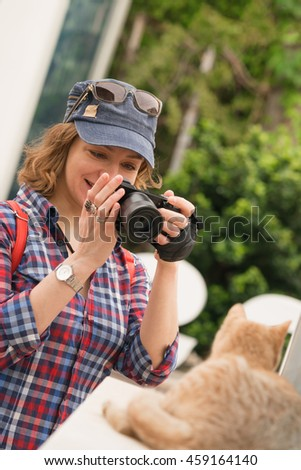 Young pretty smiling woman in a cap with a red backpack photographed ginger cat on the street. Vertical - stock photo