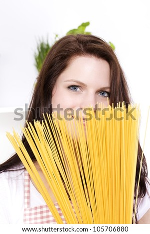 young pretty smiling woman is hiding behind some spaghetti - stock photo