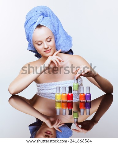 Young pretty spa woman in blue bath towel on head with nail varnish over mirror table on white background - stock photo
