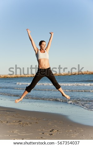 Young, pretty, sportive woman on the beach, jump (model-released)