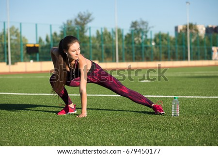 Young pretty sportswoman in sportswear stretches her legs on stadium green grass outdoors. Healthy lifestyle concept. Summer sport activity.