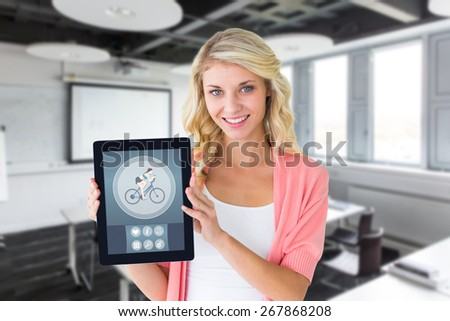 Young pretty student showing tablet pc against classroom - stock photo