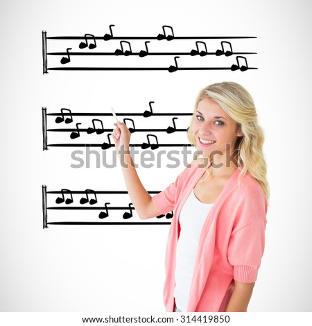 Young pretty student writing with chalk against music notes - stock photo