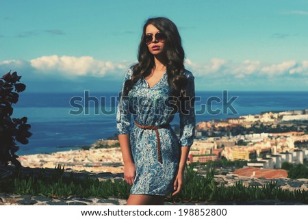 Young pretty stylish girl in blue mini dress posing against beautiful landscape with sea view. Summer fashion outdoor portrait of trendy woman. Toned image - stock photo