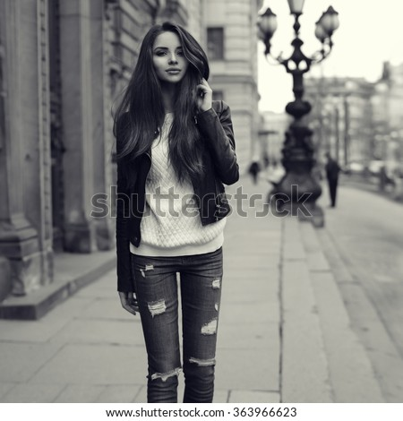 Young pretty stylish girl walking along the street. Monochrome full length portrait