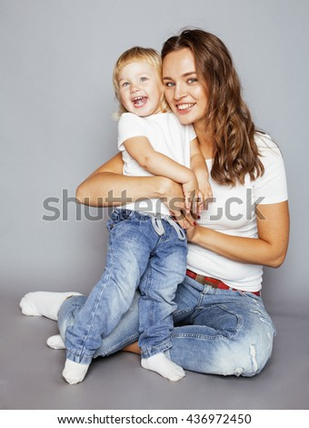 young pretty stylish mother with little cute blond daughter hugging, happy smiling family, lifestyle people concept - stock photo