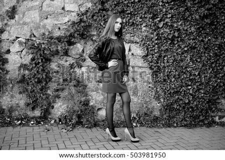 Young pretty stylish woman in high heels walking along the street. Monochrome full length portrait. Black and white