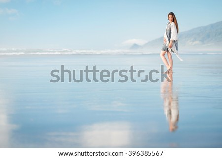 Young pretty stylish woman posing at amazing New Zealand beach with blue ocean, enjoy her vacation and summer sunny day