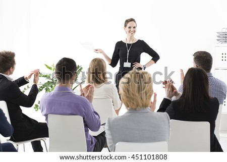 Young pretty team leader speaking in front of her colleagues during business meeting in corporation - stock photo