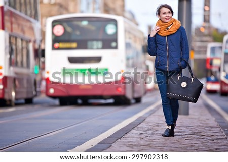 Young pretty teenage girl walking in the middle of Princess street in Edinburgh city - stock photo