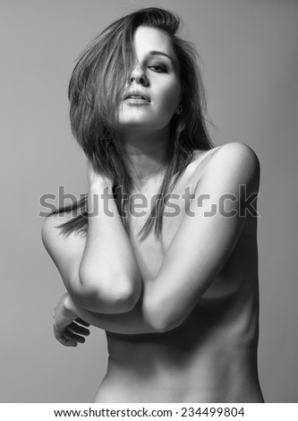 Young pretty topless woman posing on gray background - stock photo