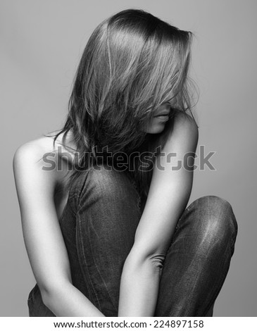 Young pretty topless woman sitting on gray background - stock photo