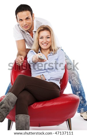 Young pretty woman and handsome man watching TV together; isolated on white - stock photo