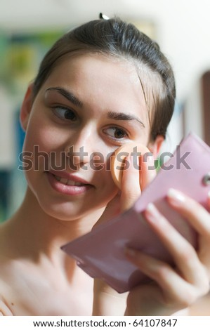 Young pretty woman applying powder on her face - stock photo