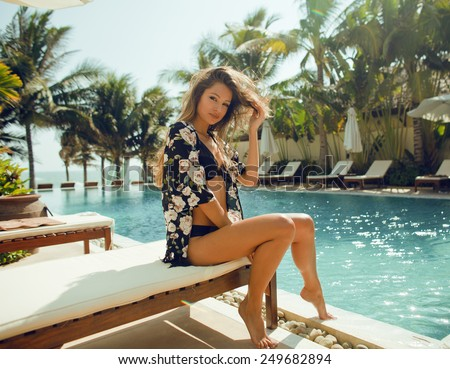 young pretty woman at swimming pool relaxing in chair, fashion look in lingerie - stock photo