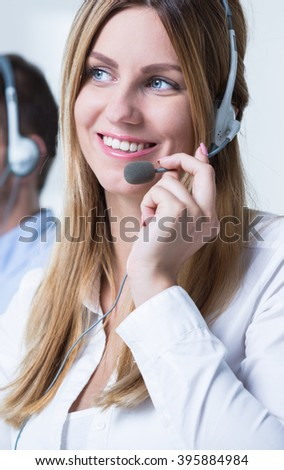 Young pretty woman at work as telemarketer - stock photo