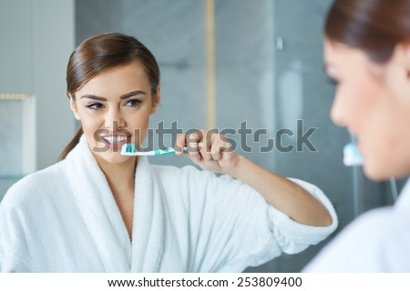 Young pretty woman brushing teeth in front of the mirror - stock photo