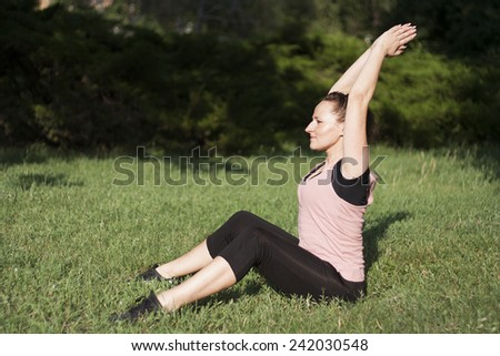 Young pretty woman doing fitness outdoors - stock photo