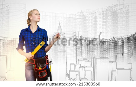 Young pretty woman engineer with tool belt on waist - stock photo
