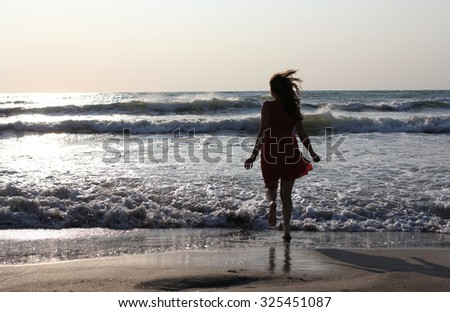 Young pretty woman enjoying the waves on the beach