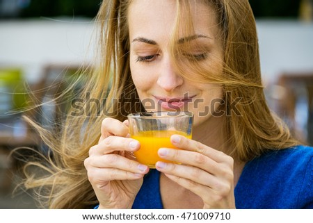 Young pretty woman enjoys cup of tea in outdoor cafe
