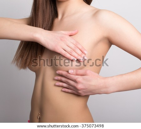 Young pretty woman examining her breast for lumps or signs of breast cancer