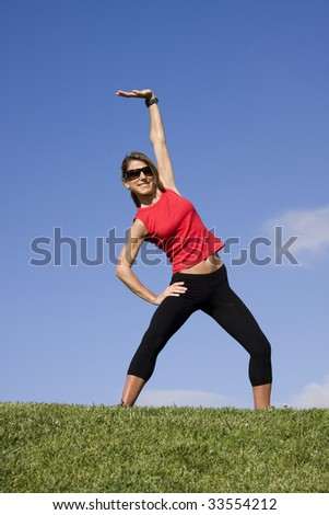 Young pretty woman exercising isolated on blue sky