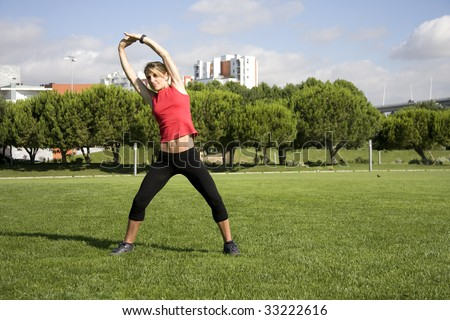 Young pretty woman exercising on the park - stock photo