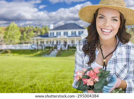 Young Pretty Woman Gardening in Front of Beautiful House. - stock photo
