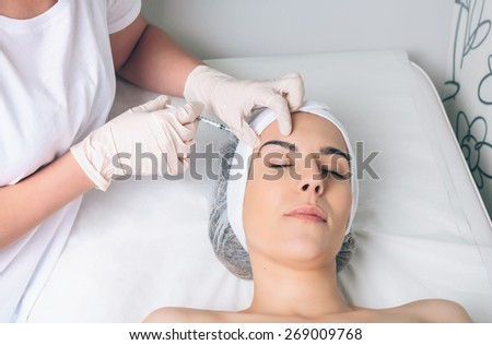 Young pretty woman getting cosmetic injection in the face like a part of the clinic treatment. Medicine, healthcare and beauty concept. - stock photo